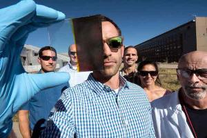 NREL's Lance Wheeler holding a sample of their switchable photovoltaic glass. Photo: NREL]